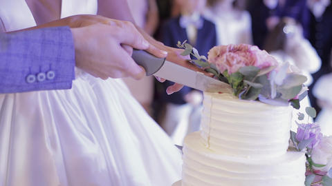 Bride and a groom is cutting their wedding cake. Hands cut of a slice of a cake Live Action