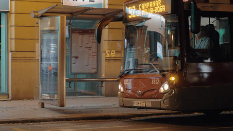 Bus leaving public transport stop in evening city. Valencia, Spain Footage