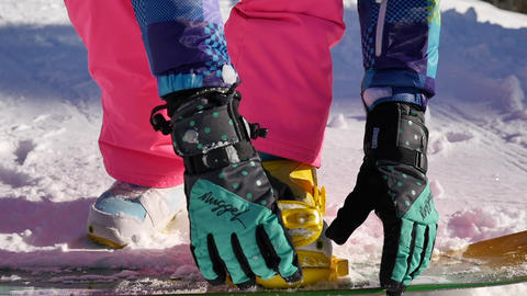 Woman snowboarder fixing legs in snowboard boots in bindings with straps on in winter ski resort. Live Action