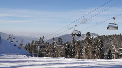 Winter ski resort concept. Ski lift for transportation skiers and snowboarders on winter mountain Footage
