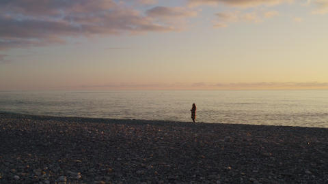 Young woman standing on pebble sea beach on evening sunset landscape. Silhouette lonely woman on sea Footage