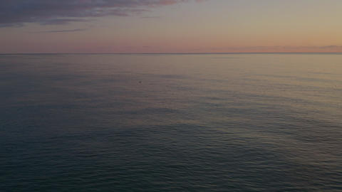Aerial view colorful sky while evening sunset over sea. Birds catching fish and flying over sea Footage