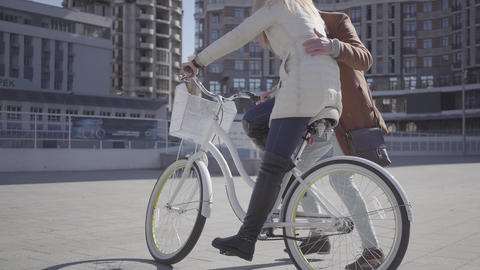 Handsome man in brown coat teaching his girlfriend to ride the bicycle in the Footage