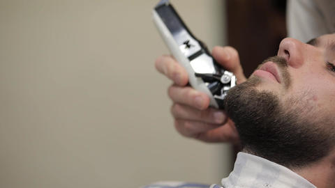Client with black beard during beard shaving in barber shop. Groom, masculine Live Action