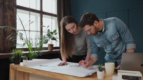 Young woman and man as an architects working with blueprints, laptop and house Live Action