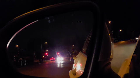 Car Side Mirror View at Night. Vehicle Rear View of Street Traffic During the Evening Live Action