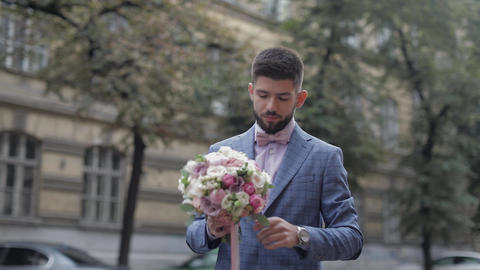Groom with a black beard with wedding bouquet on the street. Wedding day Footage