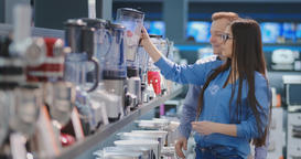 Young couple man and woman in appliances store selects a blender for their Footage