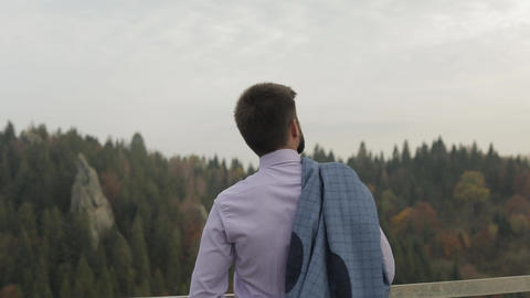 Young man on the hill of a mountain with jacket. Businessman. Bridegroom. Groom Live Action