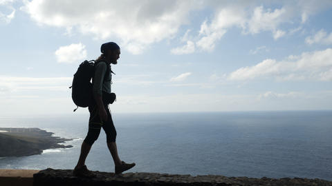 Male hiker with backpach is walking on the edge of a road in canary islands Footage
