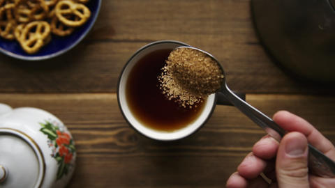 Pour cane sugar from spoon into cup of tea Footage