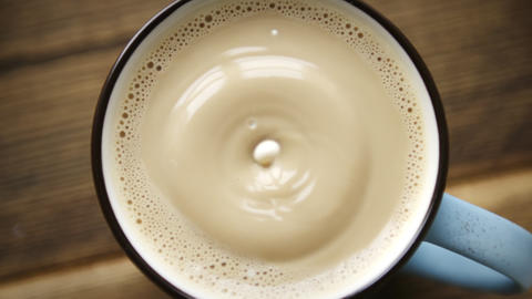 Drop of milk falls into full cup of coffee Footage