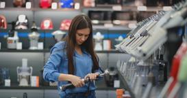 In appliances store kitchen appliances, a brunette woman in a blue shirt picks a Footage