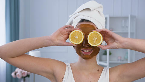 Portrait shot of attractive woman posing with two half of lemon on eyes with Live Action