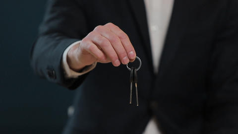 Slow motion of male's midsection in formal jacket holding house keys in hand and Footage