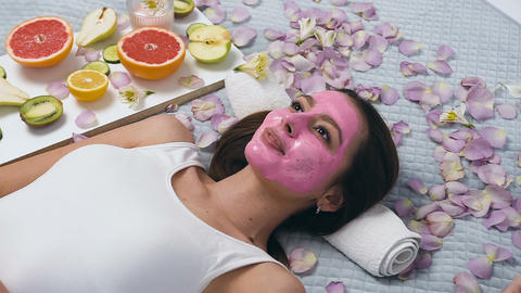 Handsome young woman with pink mask relaxing in wellness center while beautician Live Action