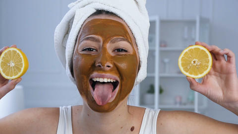 Portrait shot of attractive woman with two half of lemon on eyes with mask on Footage