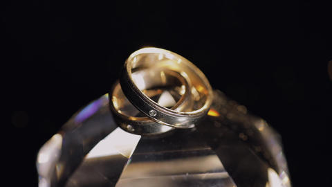 Wedding rings lying on crystal shining with light close up macro Footage