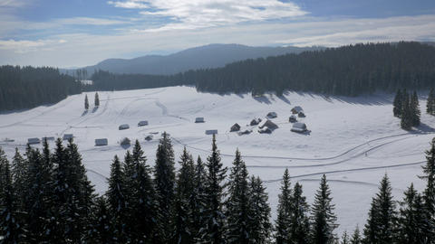 Aerial - Snowy plain plateau among forest with wooden cottages and people cross- Live Action