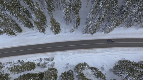 Aerial - Flying horizontally above the wintry road with a driving car Footage