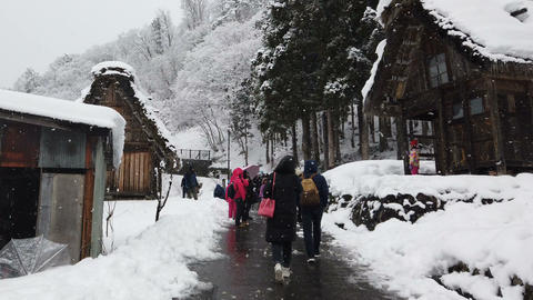 Tourists walking at historic village during snowing in winter season Live Action