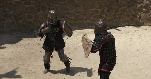 Two armored gladiators making a show with a fight on sandy arena Real Rumble GIF