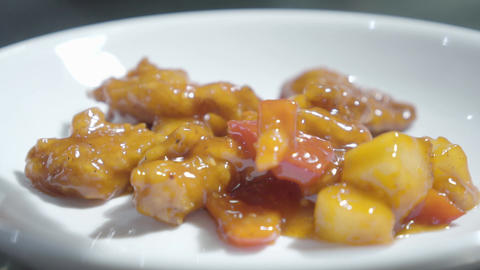 Chicken in sweet and sour sauce. Tasty dish on a white plate in an expensive Footage