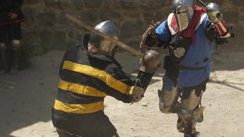 The brutal fight of two warriors in the sand arena Strikes with swords and GIF