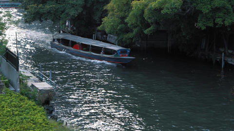 The boat floats on the city channel between green trees at summer day. Transport Footage