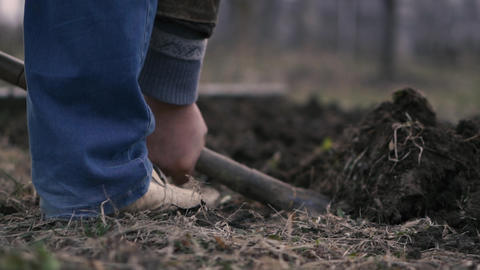 A man's leg in blue jeans is digging a shovel in the ground GIF