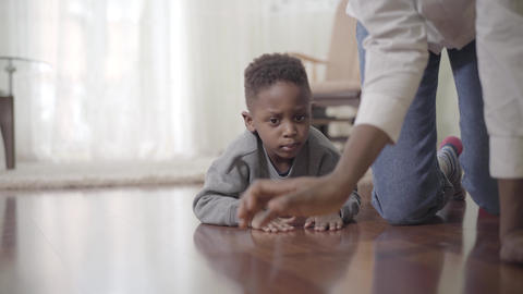 The boy crawls on the floor and his mother is nearby. African American mother Live Action