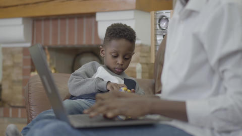 Cute African american woman working on the laptop and her little cute son Live Action