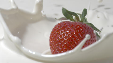 Slow motion close-up shot of a straberry falling into cream. Shot on Red Live Action