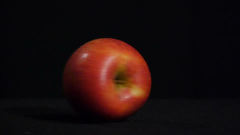 Close-up. Delicious juicy apple spins on a black background Footage