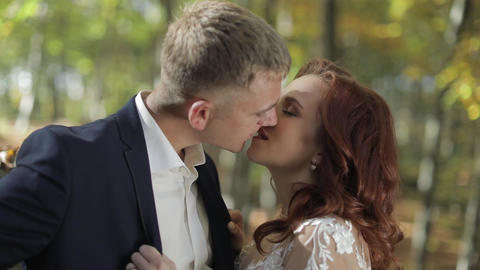 Groom with bride in the forest park. Wedding couple. Making a kiss Footage