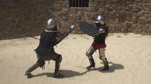 Man and woman in steel armor fighting with swords in the dusty arena Live Action
