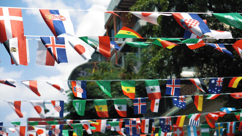 Flags of different countries are hung in the air above the street. The world Archivo