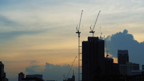 Construction cranes near unfinished skyscrapers at sunset. Building at the Live Action
