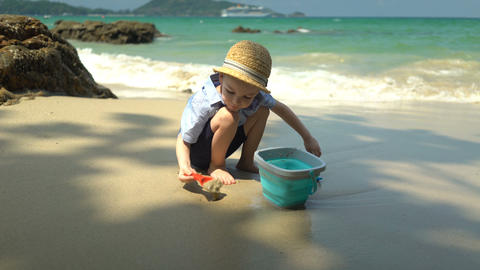 boy playing on the beach by the sea. he digs sand and throws it in the bucket Footage