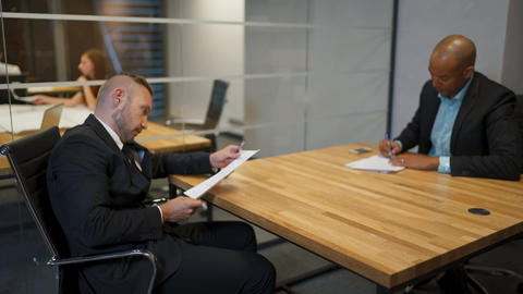 African businessman and his caucasian colleague signing employment contract in Footage