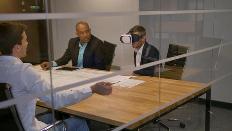 Business team sitting at a table, man with virtual reality goggles. People Footage