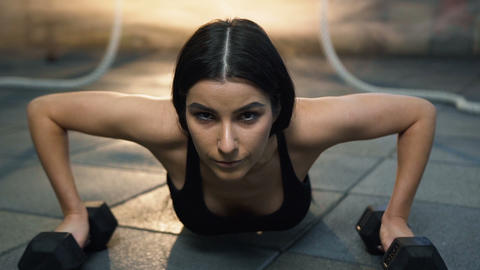 Portrait shot of attractive young woman pushing up during workout in the gym Footage