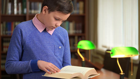 portrait shot of the cute schoolboy and standing near the bookshelf in the Footage