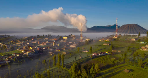 Aerial hyper lapse of mist flowing in and out of erupting Mount Bromo at sunrise Footage