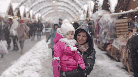 Mom and daughter are walking along the street in snowy weather Footage