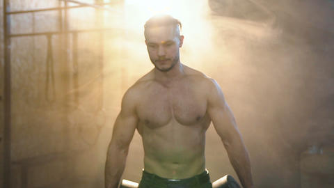 Portrait shot of muscular attractive man walking with weight plate through the Live Action