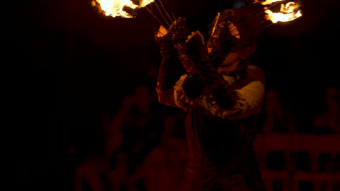 young women in masks with torches in their hands in dance at night GIF