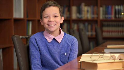 portrait shot of the cute schoolboy sits near the bookshelf in the library Footage