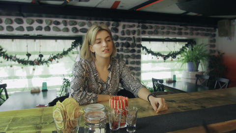 Single seductive blonde female sitting at bar counter while bartender giving Footage