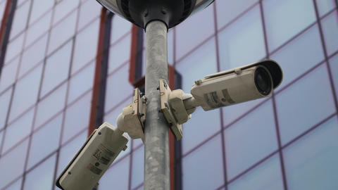 Two surveillance cameras on the light pole in front of the office building Footage